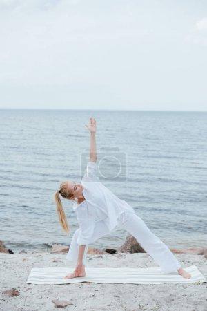 Photo pour Jolie fille avec les yeux fermés pratiquant le yoga sur le tapis de yoga près de la mer - image libre de droit