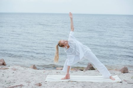 Photo pour Attractive girl with closed eyes practicing yoga on yoga mat near sea - image libre de droit