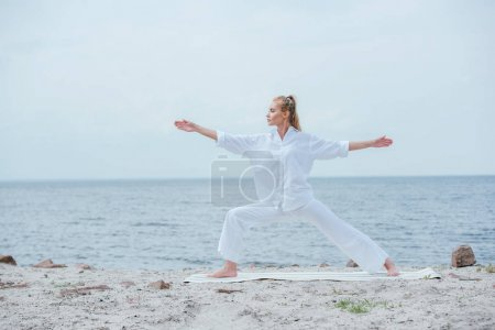 Photo pour Side view of attractive girl practicing yoga and standing with outstretched hands - image libre de droit