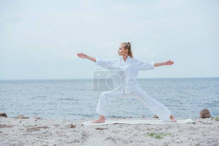 Photo pour Vue de côté de la fille attirante pratiquant le yoga et restant avec les mains tendues - image libre de droit