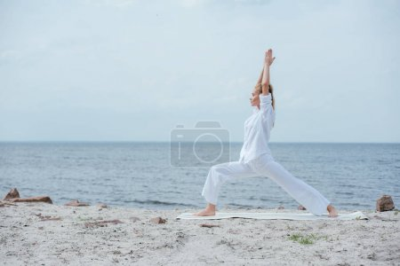 Photo for Side view of blonde woman practicing yoga near river - Royalty Free Image