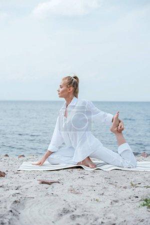 Photo pour Vue latérale de la jeune femme blonde pratiquant le yoga près de la rivière - image libre de droit