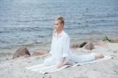 "Постер, картина, фотообои ""attractive blonde young woman practicing yoga near river on yoga mat"""
