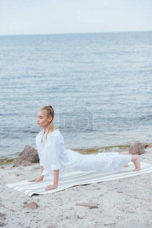 Photo pour Jeune femme blonde attirante avec les yeux fermés pratiquant le yoga près de la rivière sur le tapis de yoga - image libre de droit