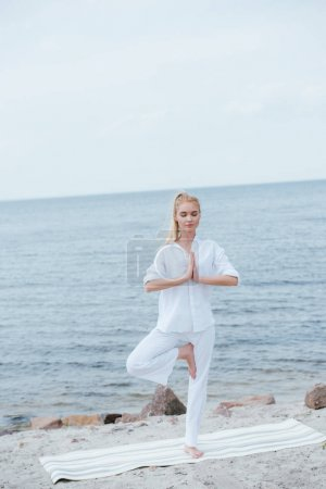 attractive blonde woman practicing yoga near river on yoga mat