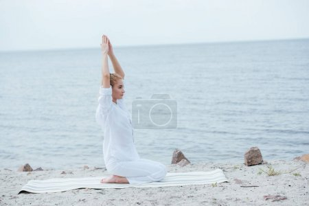 Photo pour Attractive blonde woman practicing yoga with hands above head near river - image libre de droit