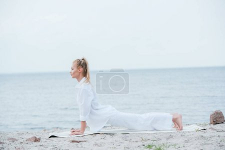 Photo pour Side view of blonde young woman practicing yoga near river on yoga mat - image libre de droit