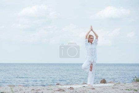 Photo pour Jolie femme blonde pratiquant le yoga avec les mains au-dessus de la tête près de la mer - image libre de droit