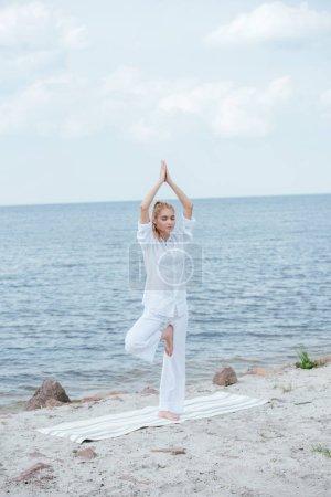 Photo pour Jolie femme blonde pratiquant le yoga avec les mains au-dessus de la tête sur tapis de yoga - image libre de droit