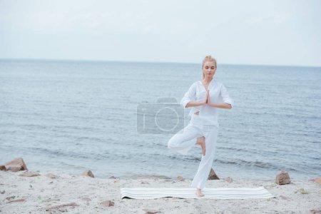 Photo pour Femme blonde avec les yeux fermés pratiquant le yoga sur le tapis de yoga - image libre de droit