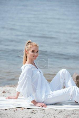 Photo pour Jeune femme blonde heureuse et attrayante assise sur un tapis de yoga - image libre de droit