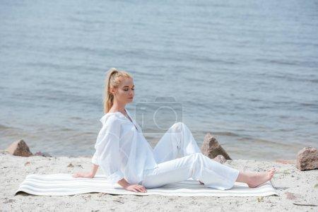 Photo pour Jolie femme blonde avec les yeux fermés assis sur le tapis de yoga - image libre de droit