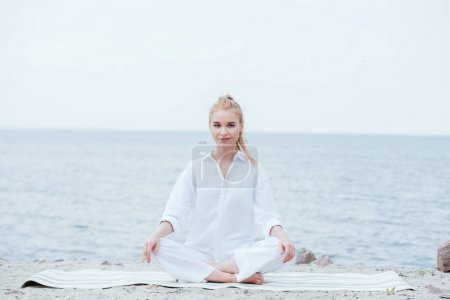 happy and beautiful blonde young woman practicing yoga near river