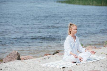 Photo pour Paisible femme blonde avec les yeux fermés pratiquant le yoga près de la rivière - image libre de droit