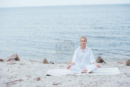 Photo pour Paisible et belle jeune femme blonde pratiquant le yoga près de la rivière - image libre de droit