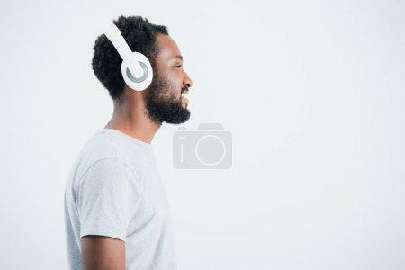 Photo pour Heureux homme afro-américain écouter de la musique avec écouteurs, isolé sur gris - image libre de droit
