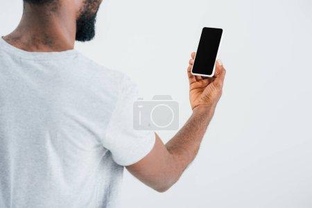 Photo pour Vue recadrée de l'homme américain africain utilisant le smartphone avec l'écran blanc, isolé sur le gris - image libre de droit