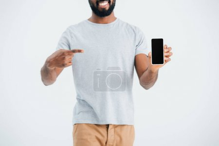 cropped view of african american man pointing at smartphone with blank screen, isolated on grey