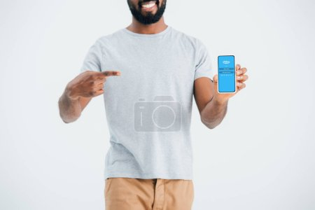Photo for KYIV, UKRAINE - MAY 17, 2019: cropped view of african american man pointing at smartphone with skype app, isolated on grey - Royalty Free Image