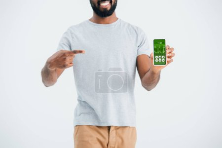 Photo pour Cropped view of african american man pointing at smartphone with health app, isolated on grey - image libre de droit