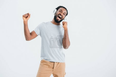 Photo for Excited african american man singing and listening music with headphones, isolated on grey - Royalty Free Image