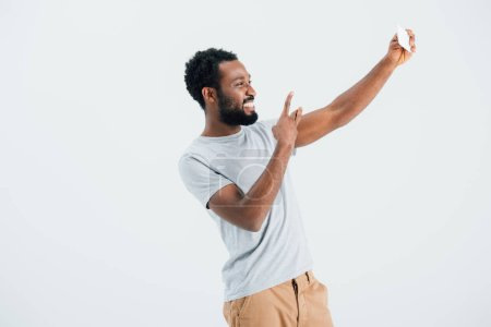 african american man with victory sign taking selfie on smartphone, isolated on grey