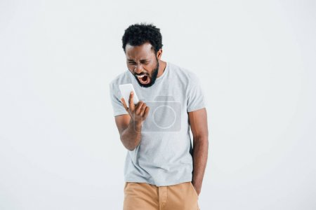 Photo for Aggressive african american man shouting and using smartphone, isolated on grey - Royalty Free Image