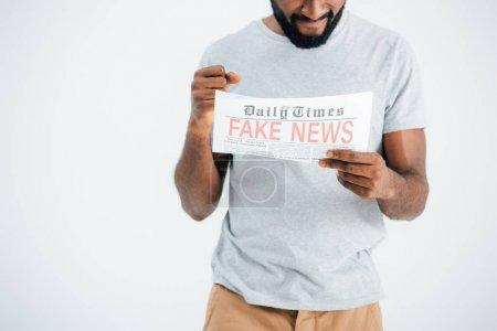 Photo pour Vue recadrée d'un homme afro-américain confus lisant un journal avec de fausses nouvelles isolées sur gris - image libre de droit
