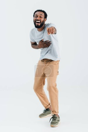 Photo for African american man laughing and pointing isolated on grey - Royalty Free Image