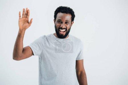 Foto de Alegre afroamericano hombre en gris camiseta ondeando aislado en gris - Imagen libre de derechos