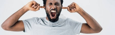 Foto de Emotional african american man in grey t-shirt yelling and closing ears isolated on grey - Imagen libre de derechos