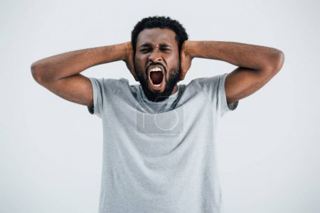 Photo for Emotional african american man in grey t-shirt screaming and closing ears isolated on grey - Royalty Free Image