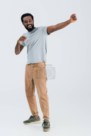Photo for Happy african american man in grey t-shirt dancing isolated on grey - Royalty Free Image