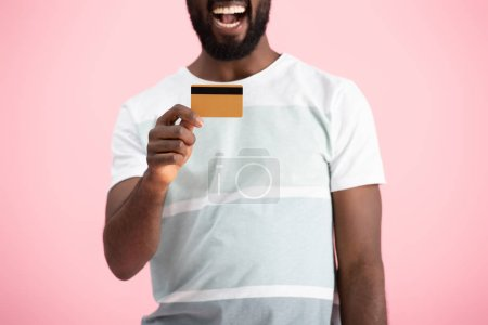 Photo for Cropped view of excited african american man showing credit card isolated on pink - Royalty Free Image