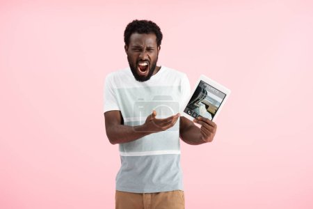 Photo for Emotional african american man screaming and showing digital tablet with tickets app, isolated on pink - Royalty Free Image