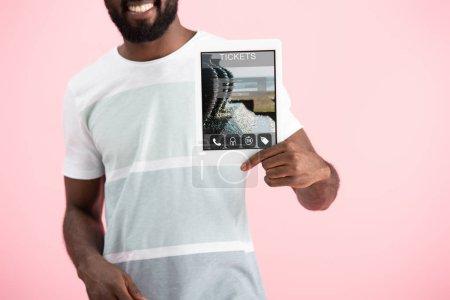 Photo pour Vue recadrée de souriant homme afro-américain montrant tablette numérique avec l'application billets, isolé sur rose - image libre de droit