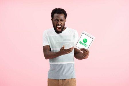 Photo pour KYIV, UKRAINE - 17 MAI 2019 : homme afro-américain émotionnel criant et montrant tablette numérique avec application spotify, isolé sur rose - image libre de droit