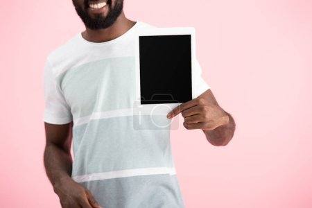 Foto de Cropped view of african american man in t-shirt showing digital tablet isolated on pink - Imagen libre de derechos