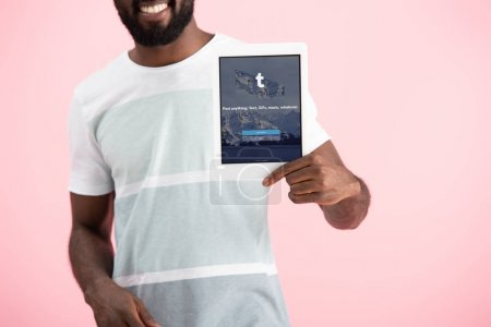 Photo for KYIV, UKRAINE - MAY 17, 2019: cropped view of african american man showing digital tablet with tumblr app, isolated on pink - Royalty Free Image