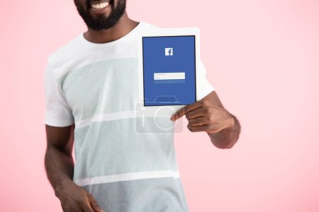 Photo for KYIV, UKRAINE - MAY 17, 2019: cropped view of african american man showing digital tablet with facebook app, isolated on pink - Royalty Free Image