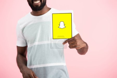 Photo for KYIV, UKRAINE - MAY 17, 2019: cropped view of african american man showing digital tablet with Snapchat app, isolated on pink - Royalty Free Image