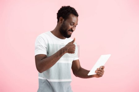 Photo pour Souriant homme afro-américain montrant pouce vers le haut tout en ayant chat vidéo sur tablette numérique isolé sur rose - image libre de droit