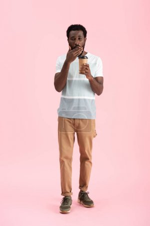 Photo for Tired african american man yawning and holding coffee to go, isolated on pink - Royalty Free Image
