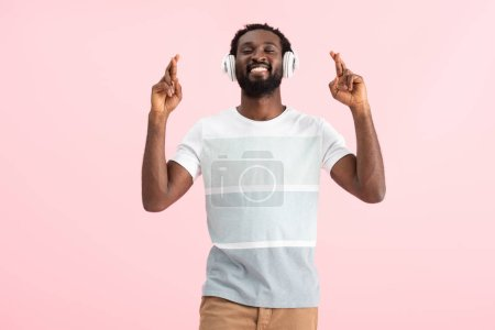 happy african american man with closed eyes and crossed fingers listening music with headphones, isolated on pink