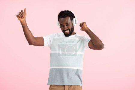 lächelnder afrikanisch-amerikanischer Mann, der mit Kopfhörern Musik hört, isoliert auf rosa