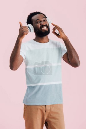 Photo pour Cheerful african american man listening music with headphones and showing thumb up, isolated on pink - image libre de droit