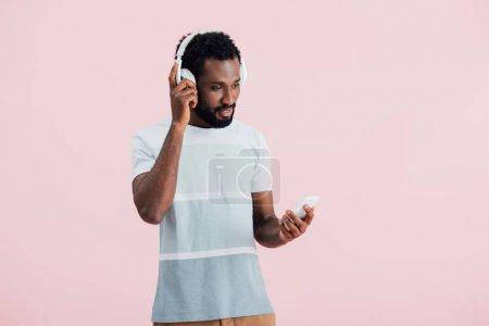 Photo pour Homme américain africain écoutant la musique avec le casque et le smartphone, d'isolement sur le rose - image libre de droit