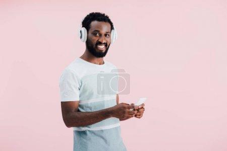 Photo pour Homme afro-américain joyeux écoutant de la musique avec écouteurs et smartphone, isolé sur rose - image libre de droit