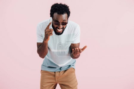 Photo for Emotional african american man in sunglasses talking on smartphone, isolated on pink - Royalty Free Image