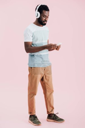 african american man listening music with headphones and smartphone, isolated on pink